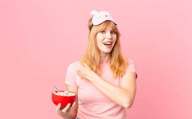 Ładna rudowłosa kobieta czuje się szczęśliwa i staje przed wyzwaniem lub świętuje w piżamie i trzyma miskę z płatkami