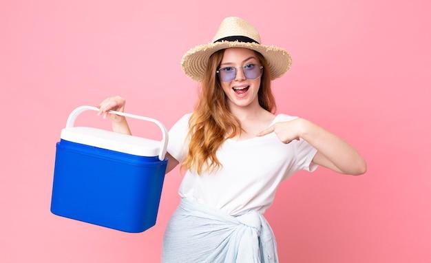Ładna rudowłosa kobieta czuje się szczęśliwa i wskazuje na siebie z podekscytowaną i trzymającą piknikową przenośną lodówkę