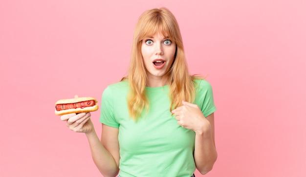 Ładna rudowłosa kobieta czuje się szczęśliwa i wskazuje na siebie z podekscytowanym i trzymającym hot doga