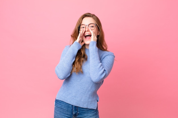 Ładna rudowłosa kobieta czuje się szczęśliwa, wydając wielki okrzyk z rękami przy ustach