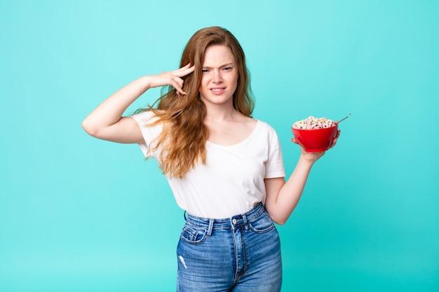 Ładna rudowłosa kobieta czuje się zdezorientowana i zdezorientowana, pokazując, że jesteś szalony i trzymasz miskę ze śniadaniem