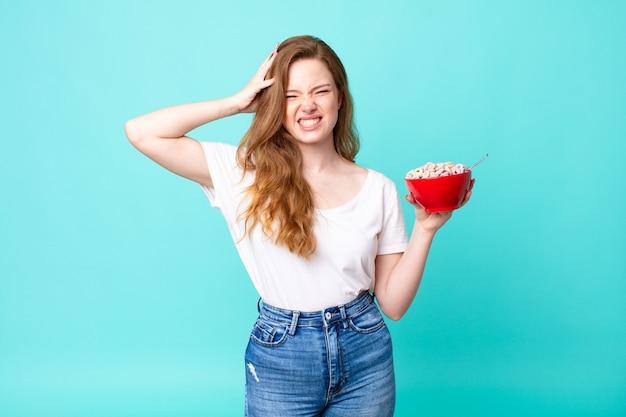 Ładna rudowłosa kobieta czuje się zestresowana, niespokojna lub przestraszona, z rękami na głowie i trzymająca miskę śniadaniową
