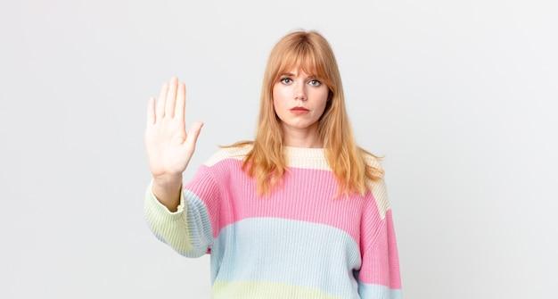 Ładna rudowłosa kobieta czuje się zestresowana, niespokojna lub przestraszona, z rękami na głowie