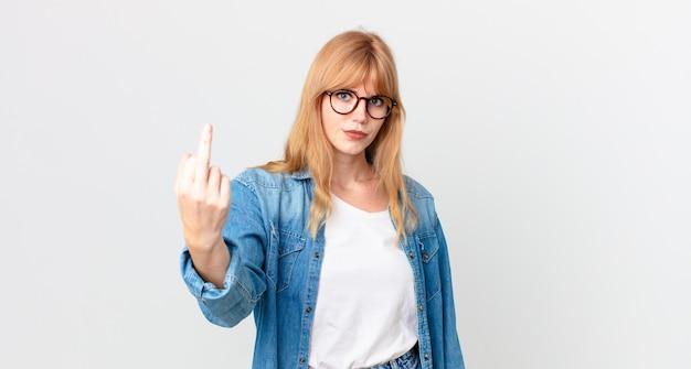 Ładna rudowłosa kobieta czuje się zła, zirytowana, buntownicza i agresywna