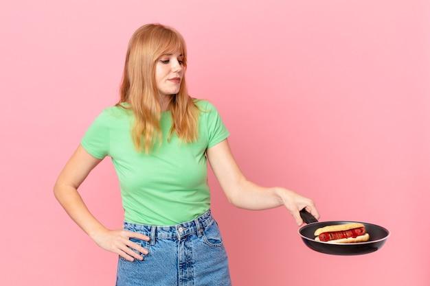 Ładna rudowłosa kobieta gotująca hot doga z patelni