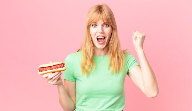 Ładna rudowłosa kobieta krzycząca agresywnie z gniewnym wyrazem twarzy i trzymająca hot doga