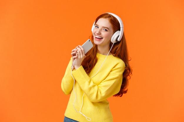 Ładna rudowłosa kobieta lubi słuchać muzyki, grając w aplikację karaoke na smartfonie