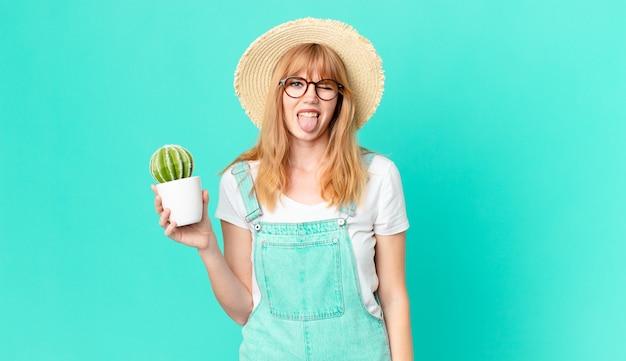 Ładna rudowłosa kobieta o wesołym i buntowniczym nastawieniu, żartująca, wystawiająca język i trzymająca kaktusa w doniczce. koncepcja rolnika
