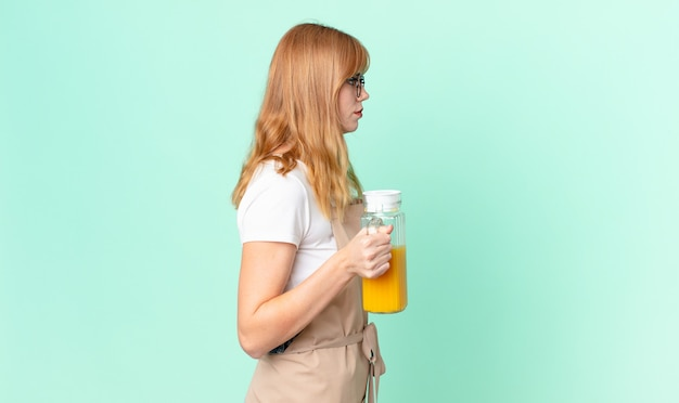 Ładna rudowłosa kobieta o widoku profilu myśląca, wyobrażająca sobie lub marząca na jawie z fartuchem przygotowującym sok pomarańczowy