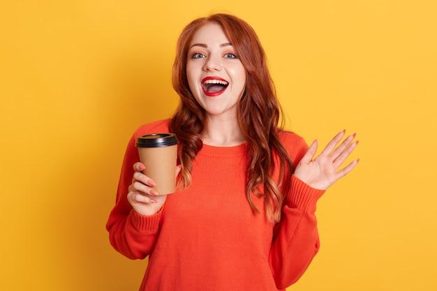 Ładna rudowłosa kobieta preferuje kawę na wynos, trzyma jednorazowy kubek z aromatycznym gorącym napojem, patrzy w kamerę z zadowolonym wyrazem twarzy i zębowym uśmiechem
