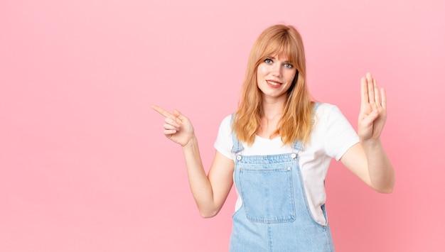 Ładna rudowłosa kobieta uśmiecha się i wygląda przyjaźnie, pokazując cyfrę cztery