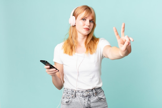 Ładna rudowłosa kobieta uśmiechająca się i wyglądająca przyjaźnie, pokazująca numer dwa i słuchająca muzyki przez słuchawki