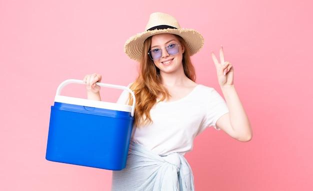 Ładna rudowłosa kobieta uśmiechająca się i wyglądająca przyjaźnie, pokazująca numer dwa i trzymająca przenośną lodówkę na piknik