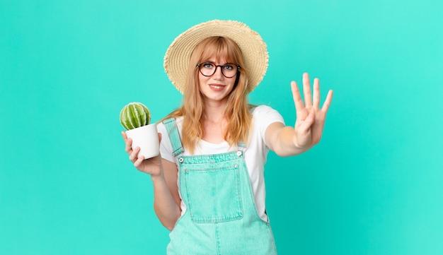 Ładna rudowłosa kobieta uśmiechnięta i wyglądająca przyjaźnie, pokazująca numer cztery i trzymająca kaktusa w doniczce. koncepcja rolnika