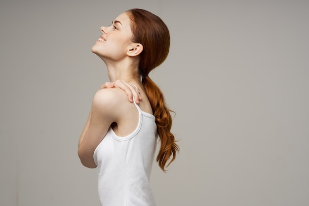Ładna rudowłosa kobieta w białej koszulce i dżinsach uśmiech studio styl życia