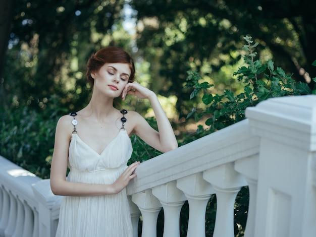 Ładna rudowłosa kobieta w białej sukni pozuje w mitologii parku