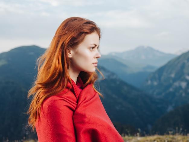 Ładna rudowłosa kobieta w górach w przyrodzie z czerwienią