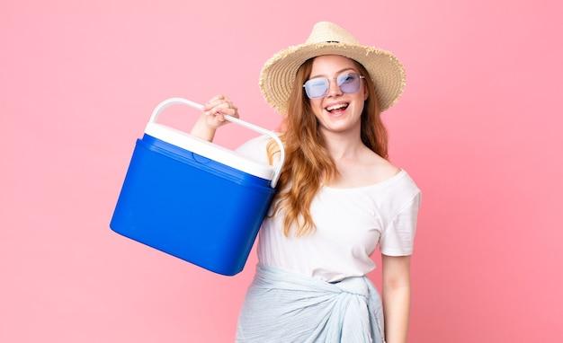 Ładna rudowłosa kobieta wygląda na szczęśliwą i mile zaskoczoną i trzyma piknikową przenośną lodówkę