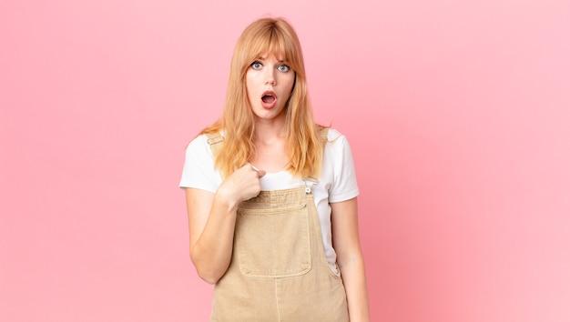 Ładna rudowłosa kobieta wygląda na zszokowaną i zaskoczoną z szeroko otwartymi ustami, wskazując na siebie
