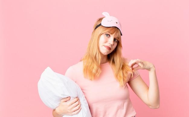 Ładna rudowłosa kobieta wyglądająca arogancko, odnosząca sukcesy, pozytywna i dumna. w piżamie i trzymając poduszkę