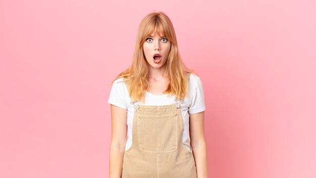 Ładna rudowłosa kobieta wyglądająca na bardzo zszokowaną lub zaskoczoną