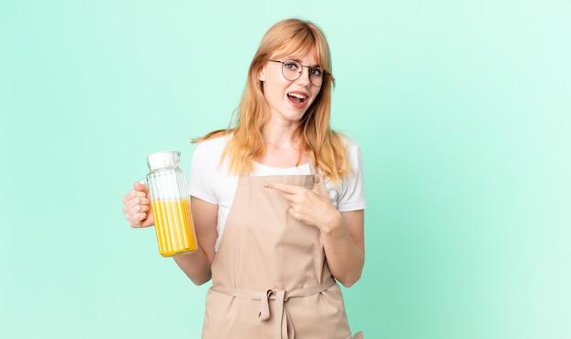 Ładna rudowłosa kobieta wyglądająca na podekscytowaną i zaskoczoną, wskazując na bok fartuchem przygotowującym sok pomarańczowy