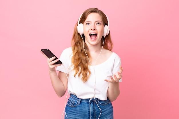 Ładna rudowłosa kobieta wyglądająca na zdesperowaną, sfrustrowaną i zestresowaną ze słuchawkami i smartfonem