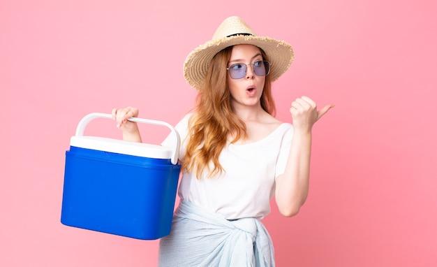 Ładna rudowłosa kobieta wyglądająca na zdziwioną z niedowierzaniem i trzymająca przenośną lodówkę na piknik