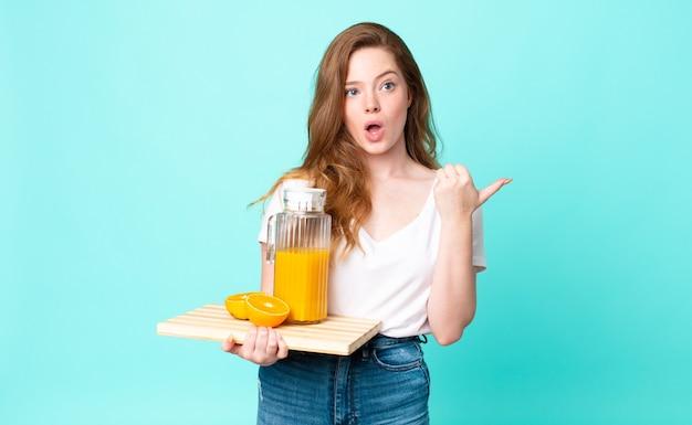 Ładna rudowłosa kobieta wyglądająca na zdziwioną z niedowierzaniem i trzymająca sok pomarańczowy