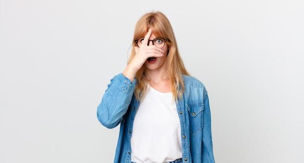 Ładna rudowłosa kobieta wyglądająca na zszokowaną, przestraszoną lub przerażoną, zakrywająca twarz dłonią