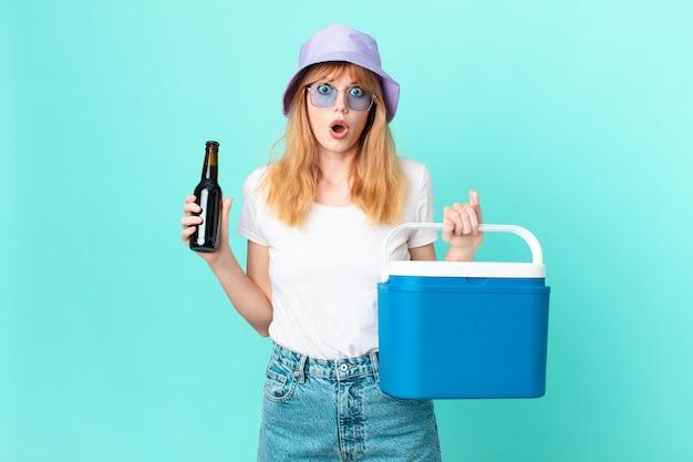 Ładna rudowłosa kobieta z przenośną lodówką i piwem