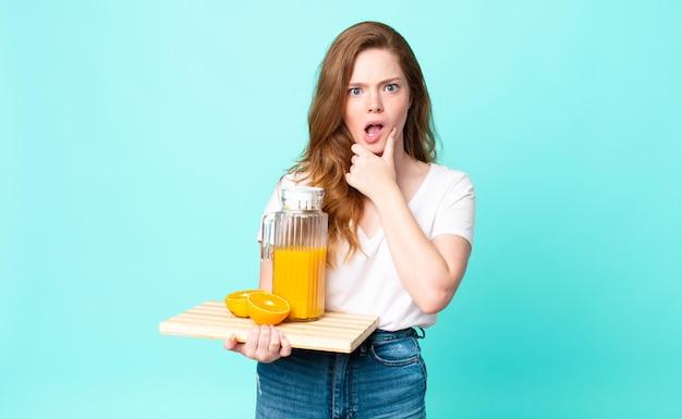 Ładna rudowłosa kobieta z szeroko otwartymi ustami i oczami, dłonią na brodzie i trzymającą sok pomarańczowy