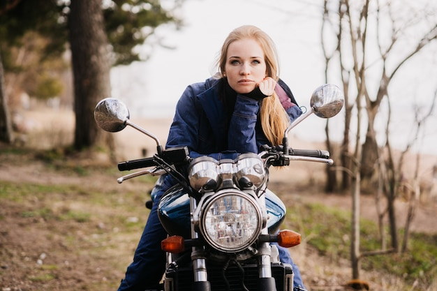 Ładna rudzielec młoda kobieta w parku, siedzi na motocyklu w zadumanym nastroju, odpoczywa podczas podróży moto. wakacje i odpoczynek.