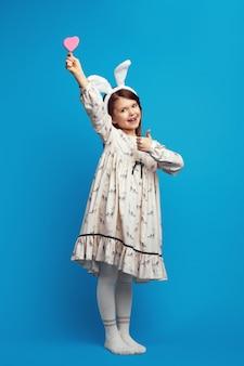 Ładna śliczna, całkiem wesoła dziewczyna trzymająca w rękach smaczne ciasteczko w kształcie serca odizolowane na niebieskiej ścianie