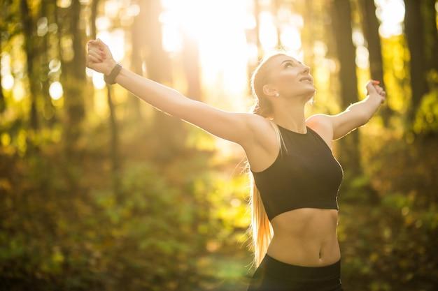 Ładna sportowa kobieta robi ćwiczenia jogi w parku