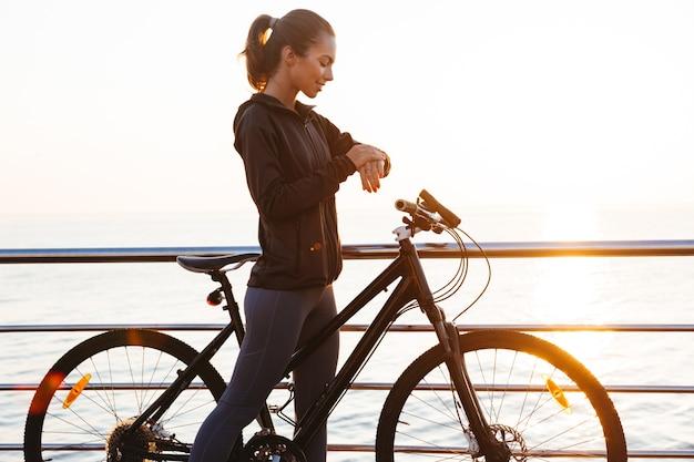 Ładna sportsmenka stojąca z rowerem na promenadzie, podczas wschodu słońca nad morzem