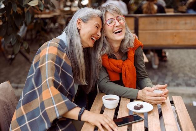 Ładna starsza azjatycka kobieta kładzie głowę na ramieniu śmiejącego się przyjaciela w ulicznej kawiarni
