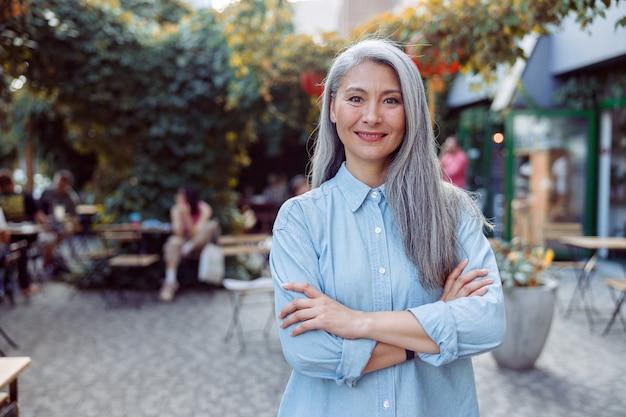 Ładna starsza azjatycka kobieta ze skrzyżowanymi rękami stoi na tarasie kawiarni na świeżym powietrzu