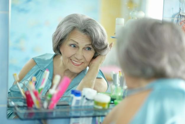 Ładna starsza kobieta robi makijaż w łazience