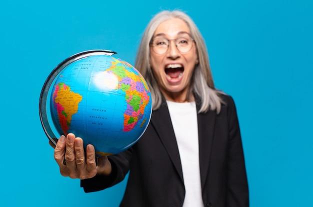 Ładna starsza kobieta z kulą ziemską. koncepcja świata