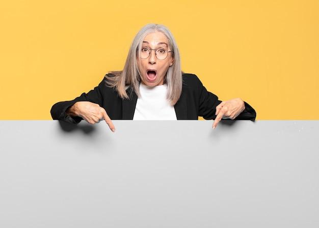 Ładna starsza kobieta z siwymi włosami wskazująca na szarą deskę