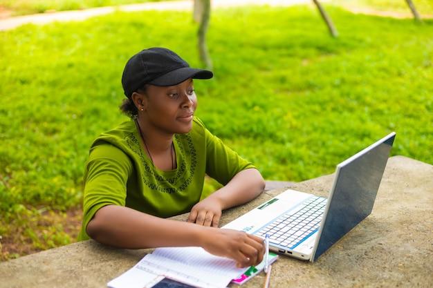 Ładna studentka na świeżym powietrzu w kampusie, korzystająca ze swojego systemu do realizacji swojego projektu