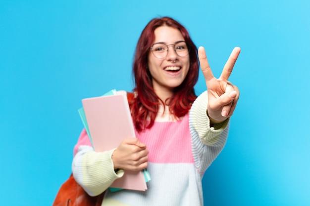 Ładna studentka robi znak zwycięstwa i trzyma zeszyty