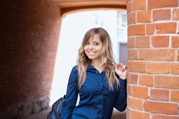 Ładna studentka w niebieskiej koszuli z pięknym uśmiechem stoi na tle ceglanego muru. ubrana w biznesowy styl