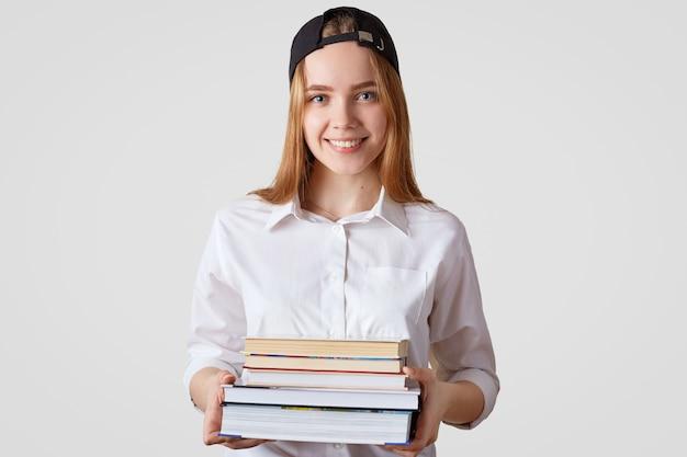 Ładna studentka z pozytywnym doświadczeniem, nosi stylową czapkę i koszulę, trzyma stos książek, idzie do biblioteki, przygotowuje się do egzaminu, na białym tle ludzie i studia koncepcja