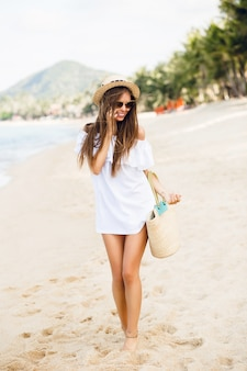 Ładna stylowa dziewczyna stojąc na plaży rozmawia na smartfonie.