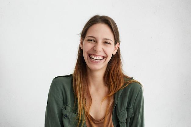 Ładna suczka ze szczerym uśmiechem ciesząca się z sukcesu w pracy, mająca dobry nastrój wyrażający pozytywne emocje