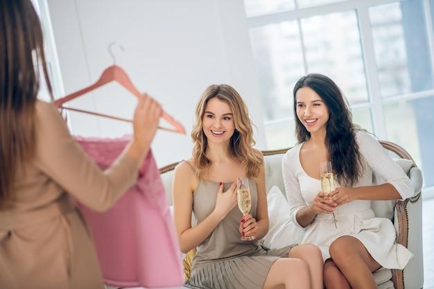 Ładna sukienka. trzy piękne dziewczyny wybierają sukienkę i wyglądają na podekscytowane
