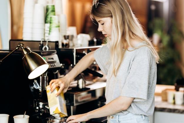 Ładna szczupła blondynka z długimi włosami, ubrana w luźny strój, gotuje kawę w nowoczesnej kawiarni. pokazano proces parzenia kawy. .