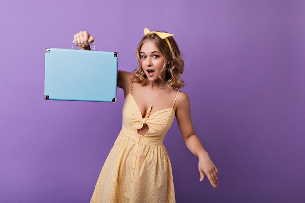 Ładna, szczupła dama o opalonej skórze pozuje z walizką. wewnątrz portret zadowolony jasnowłosej dziewczyny z niebieską walizką.
